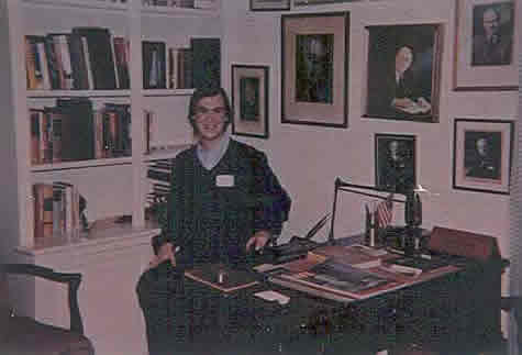 Neil sits at Mr. Byrnes' desk in the Byrnes home.